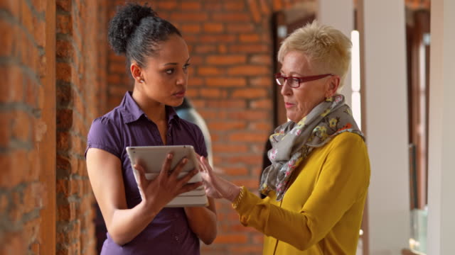 Senior woman explaining something on a tablet to her younger coworker
