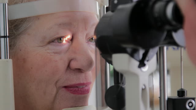 senior woman eye examination - lens optical instrument stock videos & royalty-free footage