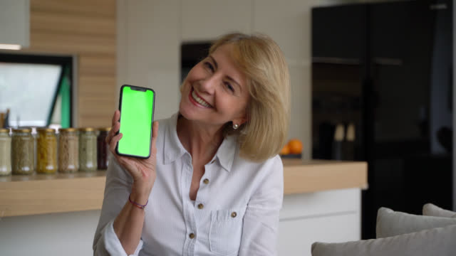 senior woman facing camera smiling and showing a screen of smartphone - chromakey - mostrare video stock e b–roll