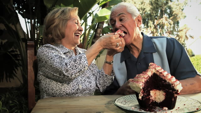 MS Senior woman feeding giant cupcake to senior man / Los Angeles, California, USA