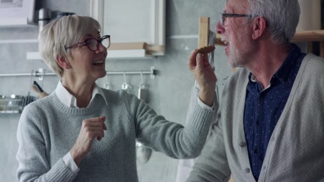 senior woman feeding her husband a gingerbread cookie - wife stock videos & royalty-free footage