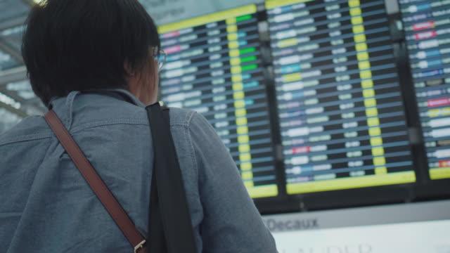 ältere frau suche nach flugzeit auf dem flughafen - flugpassagier stock-videos und b-roll-filmmaterial