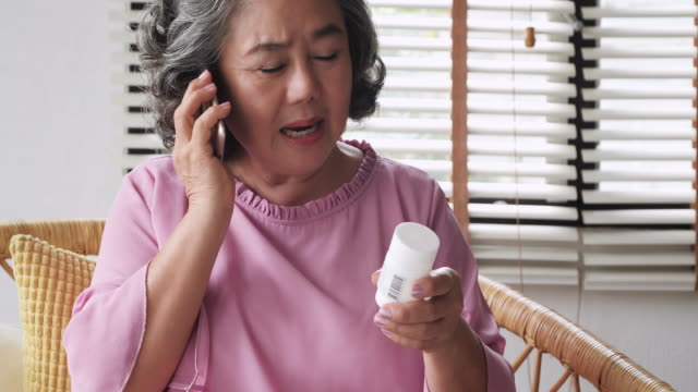 senior woman finishing refilling her prescription or conversation with her doctor or health care provider. - prescription stock videos and b-roll footage