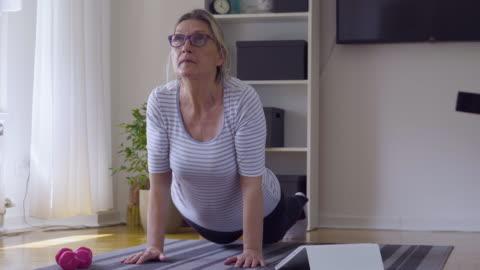 vídeos y material grabado en eventos de stock de mujer mayor siguiendo tutorial en línea y ejercicio en casa durante el aislamiento de covid - 19 en casa - bienestar