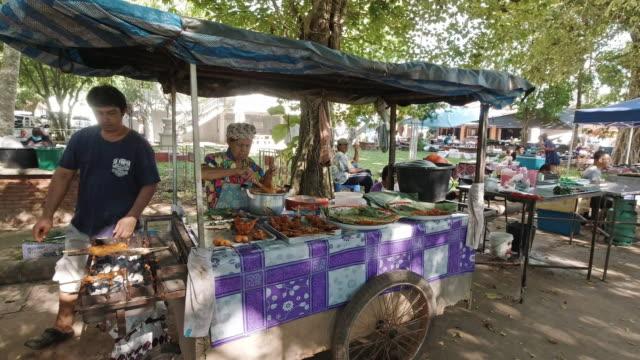vídeos de stock e filmes b-roll de senior woman fried chicken street food vendor thailand - povo tailandês