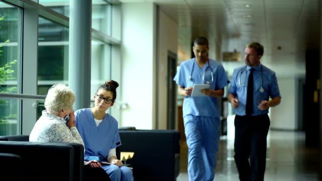 年配の女性がニュースの病院を通過します。