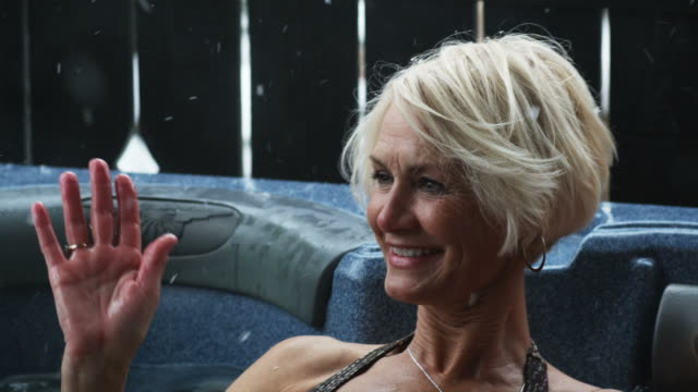 senior woman getting a snowflake in her eye while sitting in a hot tub - hot tub stock videos and b-roll footage