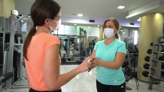 vídeos de stock e filmes b-roll de senior woman getting her hands disinfected in gym - amizade feminina