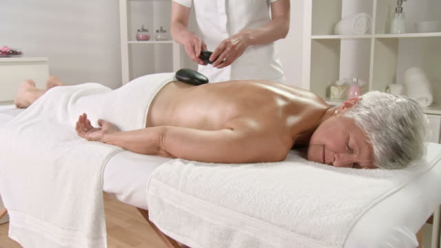 hd crane: senior woman getting lastone therapy - lastone therapy stock videos and b-roll footage
