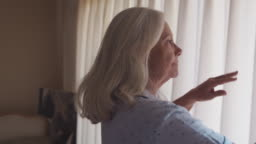 Senior Woman Getting Out Of Bed And Opening Bedroom Curtains
