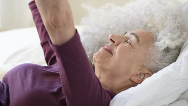 senior woman getting out of bed