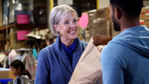 senior woman gives a bag of groceries to a young man - paper bag stock videos & royalty-free footage