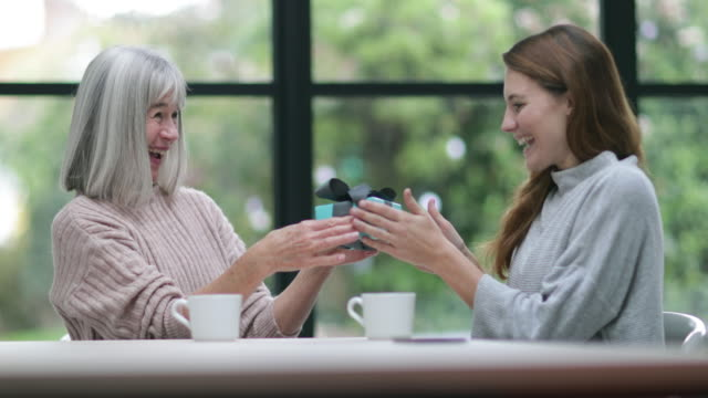 senior woman giving daughter a gift - kent england stock videos & royalty-free footage