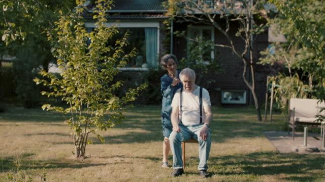 senior woman giving husband hair cut in garden of their house - cutting hair stock videos & royalty-free footage