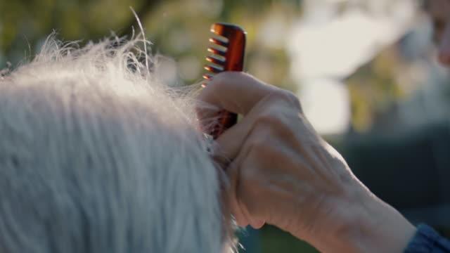 senior woman giving husband hair cut in garden of their house - human hair stock videos & royalty-free footage