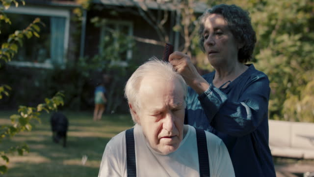 senior woman giving husband hair cut in garden of their house - illness stock videos & royalty-free footage