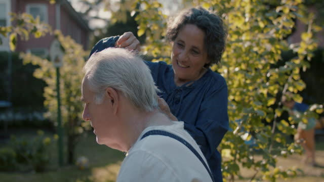 vídeos de stock e filmes b-roll de senior woman giving husband hair cut in garden of their house - apoio
