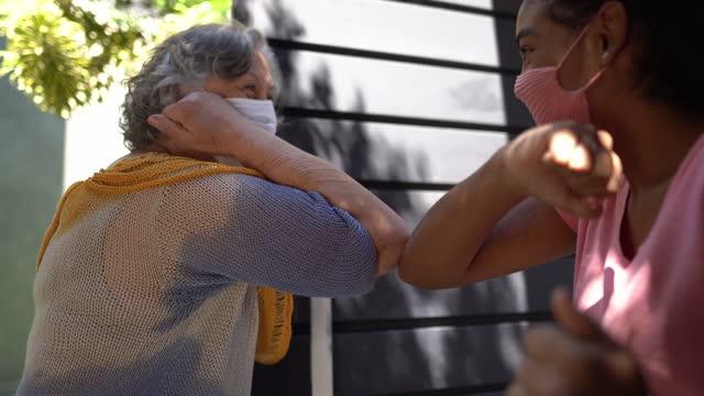 vidéos et rushes de famille aînée de salutation de femme avec la bosse de coude à la maison - masque principal de visage s'usant - arrivée