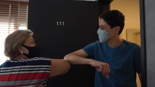 vídeos de stock, filmes e b-roll de idosa cumprimentando visitante com galo de cotovelo - usando máscara facial - encontro social