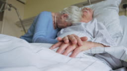 Senior woman grieving while visiting her sick husband in hospital