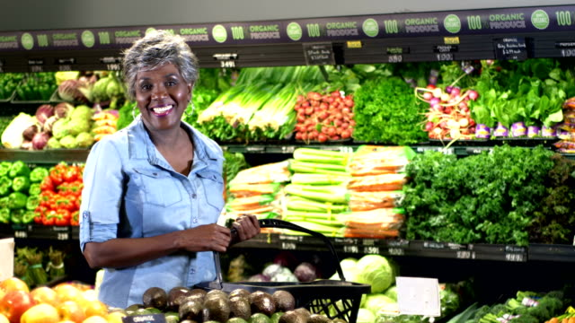 senior woman grocery shopping in produce aisle - shopping basket stock videos and b-roll footage