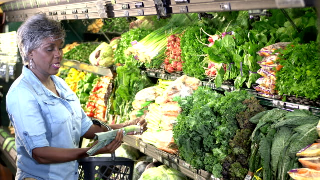 senior woman grocery shopping in produce aisle - 60 69 years stock videos & royalty-free footage