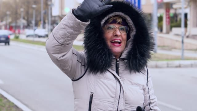 senior woman hailing a taxi in a winter day - taxi stock videos & royalty-free footage