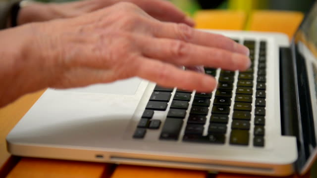 Senior woman hands typing on computer keyboard