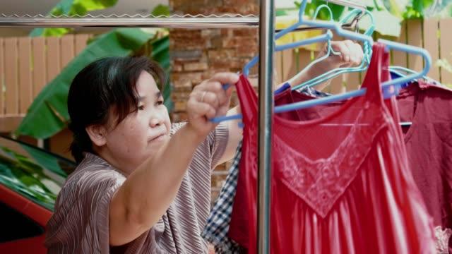 vídeos y material grabado en eventos de stock de senior mujer colgando ropa en el balcón - buena condición
