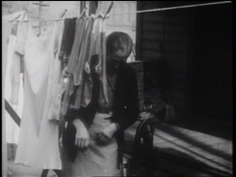 b/w 1939 senior woman hanging laundry on clothesline / starts pumping water / documentary - hausarbeit stock-videos und b-roll-filmmaterial