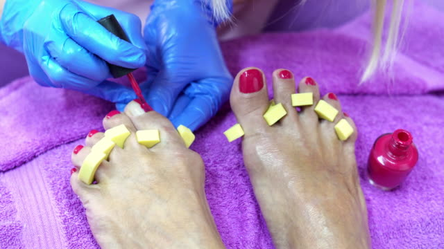 senior woman having a pedicure in a beauty spa - painting toenails stock videos & royalty-free footage