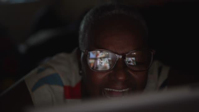 vídeos de stock, filmes e b-roll de idosa tendo uma chamada de vídeo em tablet digital em casa - escuro