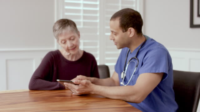 senior woman having an at home medical appointment with her mail nurse - care stock videos & royalty-free footage