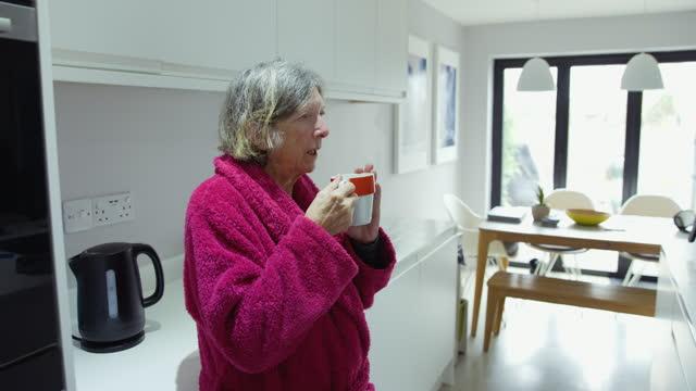 senior woman having her morning cup of tea - bathrobe stock videos & royalty-free footage