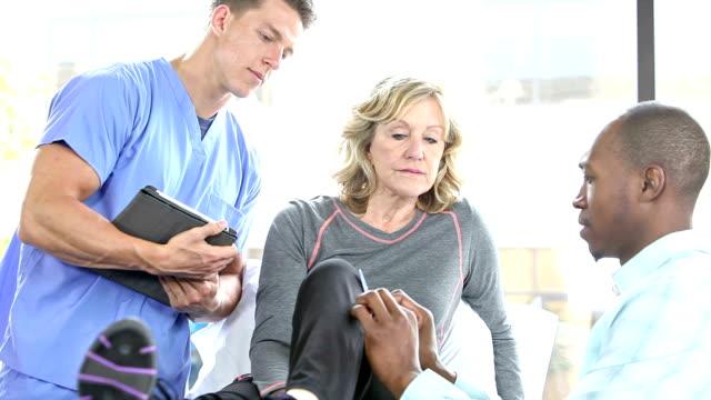 Senior woman having knee examined by orthopedic surgeon
