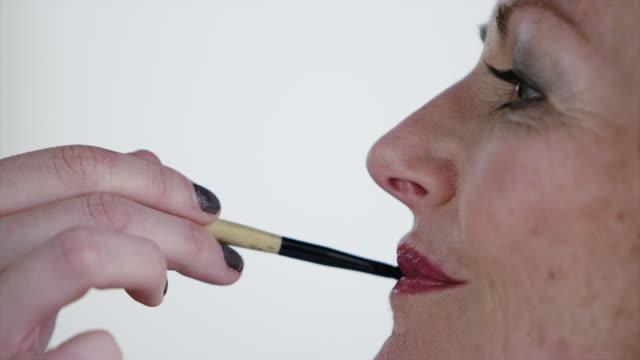CU senior woman having make up applied