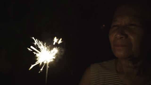 senior woman hold sparkler - flicker bird stock videos and b-roll footage