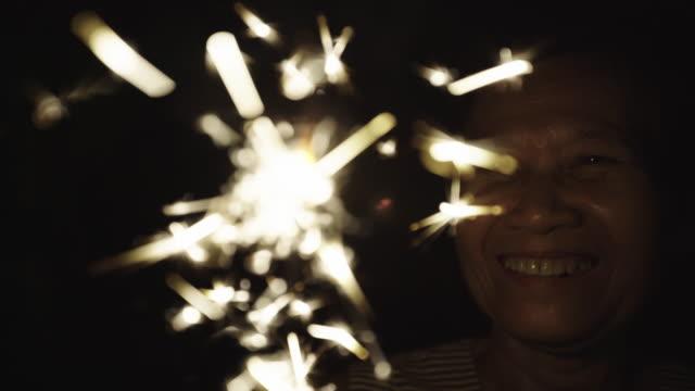 senior woman hold sparkler - flicker bird stock videos & royalty-free footage