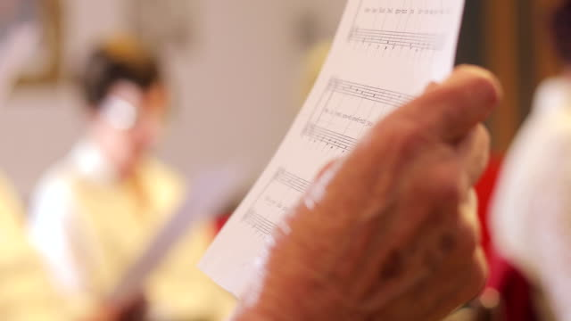 senior woman holding a note sheet while singing - choir stock videos & royalty-free footage
