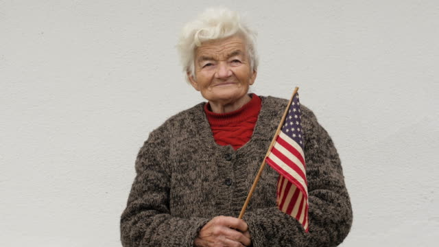 senior woman holding american flag looking at camera and smiling - citizenship stock videos & royalty-free footage