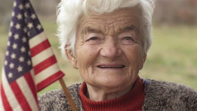 Senior Woman Holding American Flag Looking at Camera and Smiling