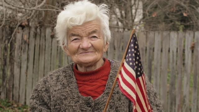 Senior vrouw met Amerikaanse vlag op zoek op Camera en glimlachen