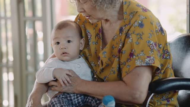 senior woman holding grandson - grandparent stock videos & royalty-free footage
