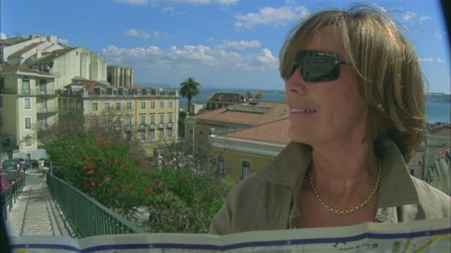 vídeos de stock, filmes e b-roll de cu, senior woman holding map, cityscape in background, alfama, lisbon, portugal - jovem de espírito