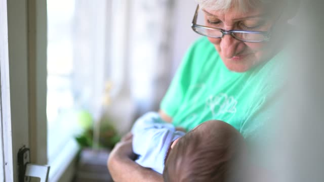 senior woman holding newborn baby - grandparent stock videos & royalty-free footage