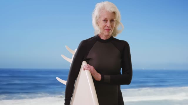senior woman holding surfboard at scenic beach looking at camera confidently - old diving suit stock videos and b-roll footage