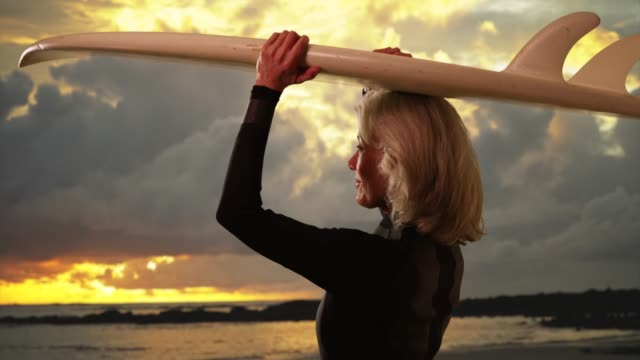 senior woman holding surfboard enjoying view of sunset at the beach smiling - old diving suit stock videos and b-roll footage