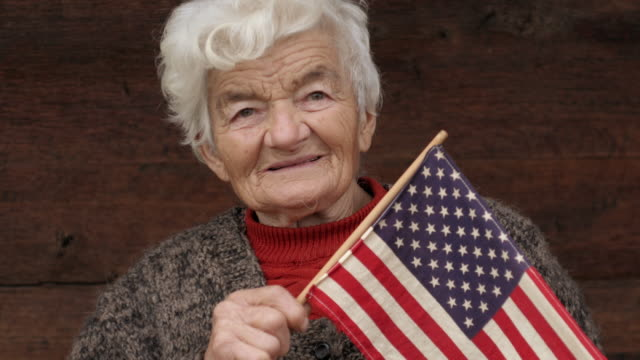 senior woman holding usa flag looking at camera and smiling - voting booth stock videos and b-roll footage