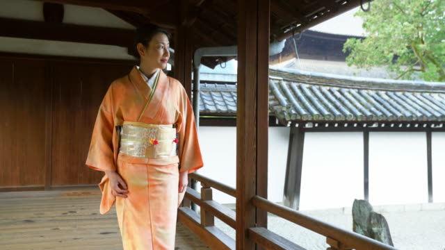 senior woman in a kimono taking a peaceful walk through a temple - shrine stock videos and b-roll footage