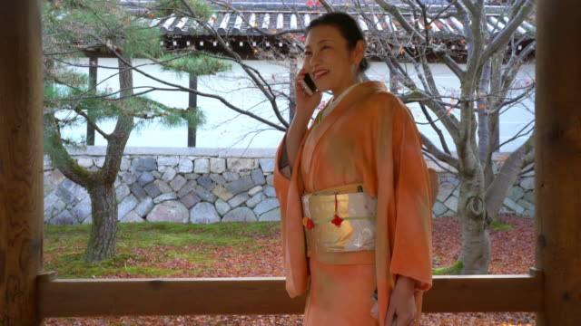 senior woman in a kimono walking through a temple talking on the phone - kyoto temple stock videos and b-roll footage